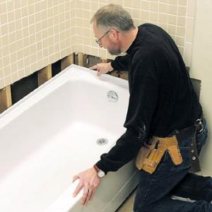 Сантехник устанавливает ванну
