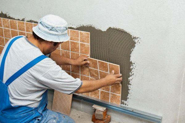 Мастер укладывает плитку в ванной на стену