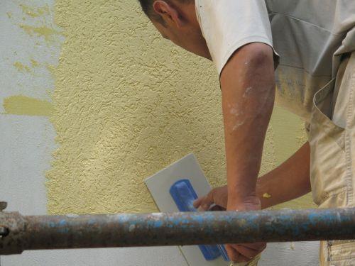 Мастер штукатурит стену короедом